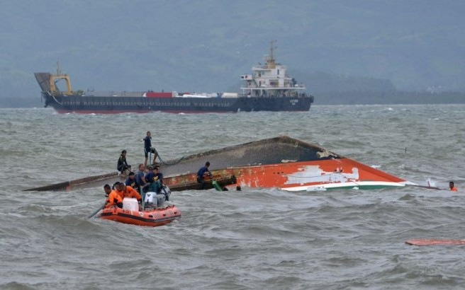Rescuers tie a rope at the capsized vessel MBCA Kim-Nirvana to pull it towards the shore near a port in Ormoc