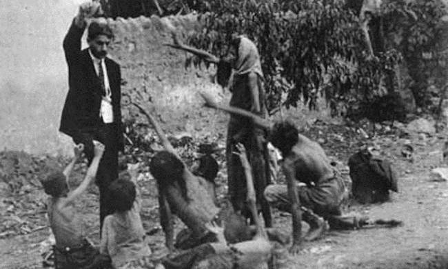 704330-turk_official_teasing_armenian_starved_children_by_showing_bread_1915_.jpg