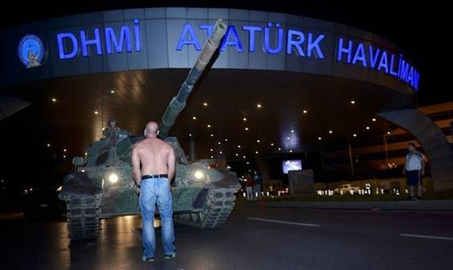 713541-a-man-stands-in-front-of-a-turkish-army-tank-at-ataturk-airport-in-istanbul.jpg