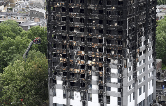 LONDON, ENGLAND - JUNE 16:  Firefighters inspect the remains of Grenfell Tower from a cherry picker on June 16, 2017 in London, England. 30 people have been confirmed dead and dozens still missing after the 24 storey residential Grenfell Tower block in Latimer Road was engulfed in flames in the early hours of June 14. Emergency services will spend a third day searching through the building for bodies. Police have said that some victims may never be identified.  (Photo by Carl Court/Getty Images)